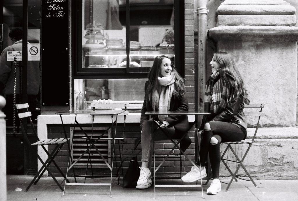 two girls sitting outside a french coffee shop laughing