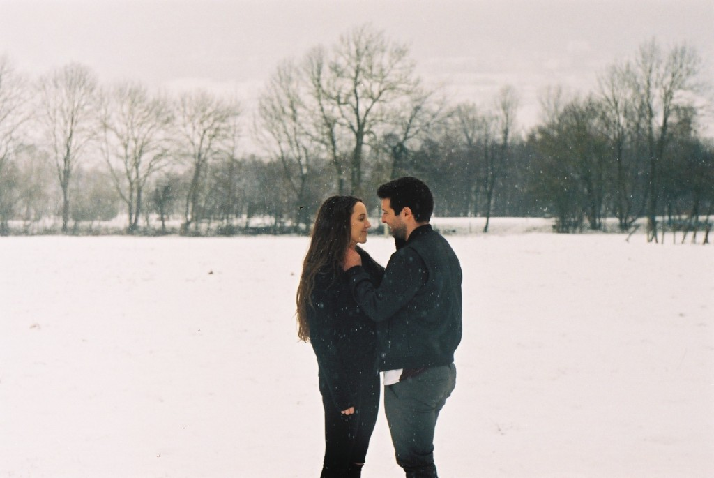 couple standing together in the snow, hands in each others face